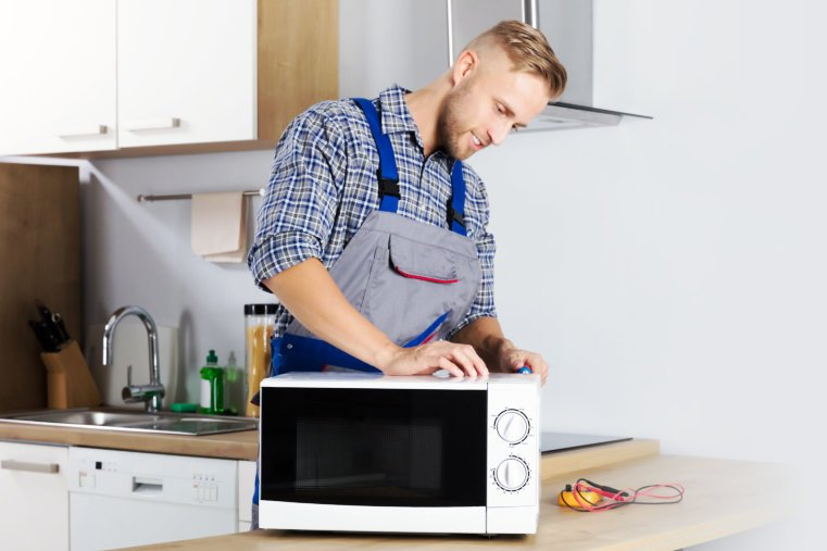 technician fixing oven